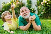 Child With Grandfather Dreams In Summer In Nature. Happy Child With Grandfather Playing Outdoors. Gr poster
