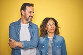 Beautiful middle age couple together wearing denim shirt over isolated yellow background smiling loo poster