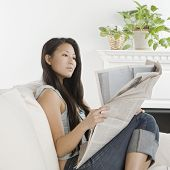 Young Asian woman reading newspaper on sofa