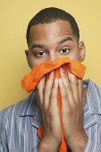 African man in pajamas holding washcloth to face