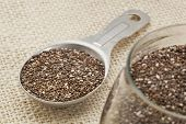foto of tablespoon  - chia seeds in glass jar and on measuring aluminum tablespoon against burlap background - JPG