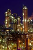 Chemical Production Facility At Night With Lots Of Pipes