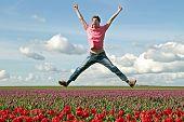Chico joven entusiasta saltar desde los campos de tulipanes en Holanda