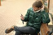 Hipster Use Smartphone On Winter Day. Man Handsome Hold Smartphone. Guy Sit Bench Interact Smartphon poster
