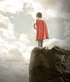 stock photo of crusader  - A young super hero boy is wearing a red cape and standing on a rocky cliff looking at a cloudy sky with copyspace - JPG
