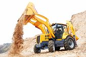 Wheel loader Excavator with backhoe unloading sand at eathmoving works in construction site