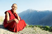stock photo of saffron  - Two Indian tibetan old monks lama in red color clothing sitting in front of mountains - JPG