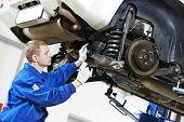 car mechanic inspecting car wheel and suspension detail of lifted automobile at repair service stati