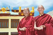 Two Indian tibetan old monks lama in red color clothing standing in front of monastery