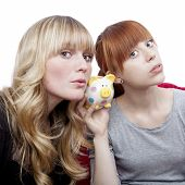 Young Beautiful Blond And Red Haired Girls Ears On Moneypig On Red Sofa In Front Of White Background