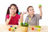 Dos niños pintan huevos de Pascua