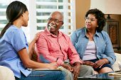 picture of visitation  - Nurse Making Notes During Home Visit With Senior Couple - JPG