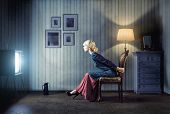 image of scared  - Young  woman sitting on a chair in vintage interior  and watching retro tv - JPG