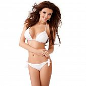 Vivacious sexy young brunette woman with a beautiful smile and her hair blowing in the breeze posing in a white bikini  three quarter isolated studio portrait