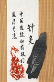 stock photo of qi  - Acupuncture needles with sandalwood and mandarin script on rice paper over bamboo - JPG