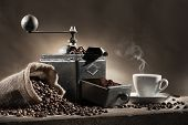 stock photo of hot coffee  - coffee beans in jute bag with coffee grinder and hot cup of coffee on wooden table