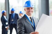senior construction engineer holding blue print