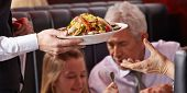 Hand of waiter serving seafood salad to elderly woman