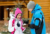 Couple having fun outdoors during winter vacations and playing at snowballs
