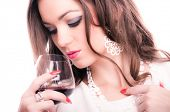 Beautiful brunette with curly hair holding glass of red wine, isolated on white