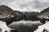 Alpine Lake Ritsa In Winter Under Gloomy Clouds, Abkhazia