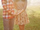 stock photo of jeans skirt  - Happy couple holding hands looking in the sunset - JPG