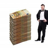 Man Standing Next To Huge Stack Of Money