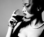 portrait of beautiful young woman with wine glass, black and white retro stylization