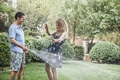 Couple playing in garden with water hose