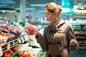 picture of department store  - Beautiful young woman shopping for fruits and vegetables in produce department of a grocery store - JPG