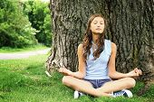 Teenager doing yoga and relaxing by siting in a grass in a park on a huge and old tree.