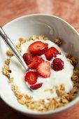Fresh strawberries and muesli in a white bowl