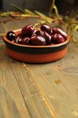 Kalamata olives into in a ceramic bowl on wooden table