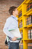 Side view of young male student holding books while looking at shelf in college library