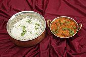 Lamb rogan josh, served with jeera (cumin) rice in beaten copper bowls. A tilt-shift lens has been u