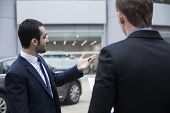 Car salesman holding car keys and selling car to young businessman
