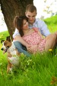 Couple Is Sitting On A Green Meadow