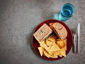 a well balanced healthy diet of a turkey sandwich with tortilla chips and a glass of water in a nice