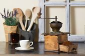 stock photo of coffee grounds  - Old vintage manual coffee mill or grinder with a drawer full of freshly ground coffee beans standing on an old wooden kitchen counter with a cup and saucer ready to brew a morning drink - JPG