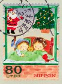 JAPAN - CIRCA 1990th: A stamp printed in Japan, shows children at Christmas tree, circa 1990th
