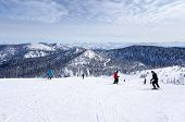 stock photo of descending  - Skiers descending from the summit at Whitefish - JPG