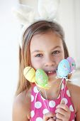 Portrait of a pretty little girl wearing bunny ears holding Easter eggs