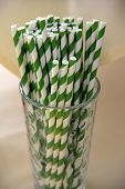 Glass filled with green and white straws