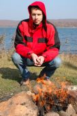 Young Blond Man In Red Jacket Sit Near Fire.
