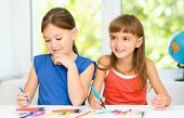Little girls are drawing using felt- tip pens while sitting at table