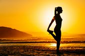 stock photo of morning  - Fitness woman exercising and stretching legs on beautiful summer sunset or morning at beach - JPG