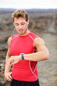 Running man looking at heart rate monitor GPS watch. Runner listening to music in earphones wearing