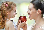 mother and daughter holding red apple