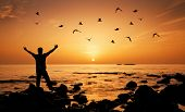 picture of single man  - Man feeling freedom on beach during sunrise - JPG