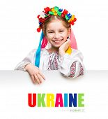 stock photo of national costume  - little girl in the Ukrainian national costume behind white board with space for text - JPG